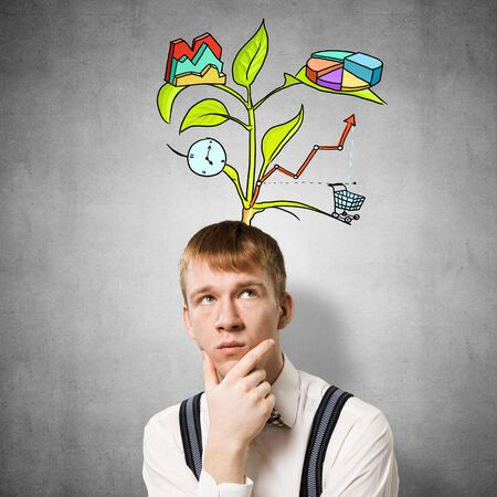 Redhead student looks pensive upwards and thinking about some genius idea. Clever boy with drawing ideas tree above head. Young scientist on background of grey wall. Idea generation process. Reklamní fotografie