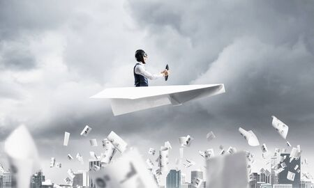 Crisis management and control in difficult situation concept. Businessman in aviator hat driving paper plane in storm. Pilot flying in small airplane. Megalopolis panorama with dramatic sky. Stok Fotoğraf