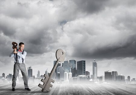 Determined businessman against modern cityscape breaking with violin stone key figure Imagens