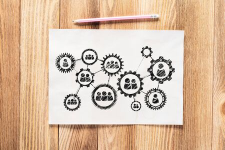 Business process management pencil hand drawn with group of rotating cogwheels. Human resources sketch on wooden desk. Workplace with paper and pencil on wooden desk. Social communication infographics