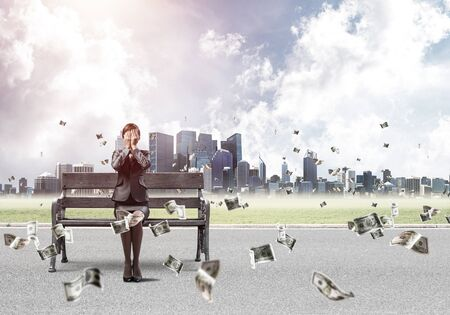 Young woman sitting on wooden bench outdoor. Girl in business suit keeps hands on face for surprise. Hide from problems. Help and successful solutions. Cityline panorama with falling money banknotes