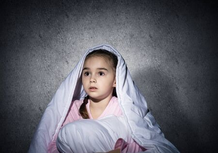Frightened girl hiding under blanket. Scared kid lying in his bed at home. Fear of the dark. Beautiful little girl can not sleep at night. Portrait of child in pajamas on background of grey wall.