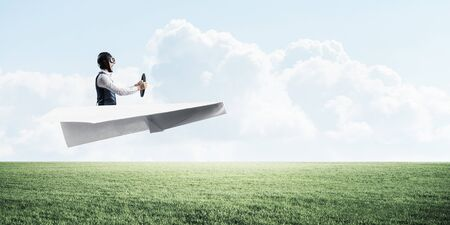 Happy aviator driving small paper plane on background of natural landscape. Man in big paper airplane flying low above green meadow. Nature panorama with green grass and cloudy sky in summer day.