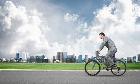 Businessman hurry to work by bike. Man wearing business suit riding bicycle on countryside asphalt road. Cyclist on background of cityscape and blue sky. Eco-friendly transport and outdoor activity