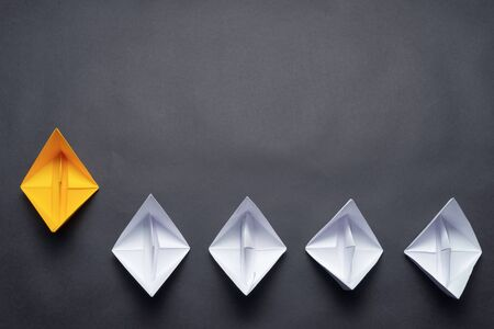Row of paper ships on black background. Business concept of creative innovation and leadership. Flat lay yellow origami leader boat ahead others boats. Social marketing layout with copy space.