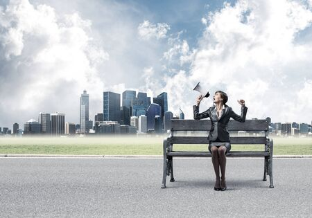 Business woman with megaphone sitting on wooden bench. Female speaker shouting in loudspeaker outdoors. Modern cityline panorama in sunny day. Business marketing and announcement.