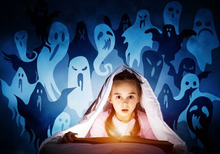 Scared kid with reading book under blanket. Afraid girl lying in bed at home. Child reading scary stories. Girl in pajamas and imaginary ghosts back on night sky. Bright light shining from open book. 免版税图像