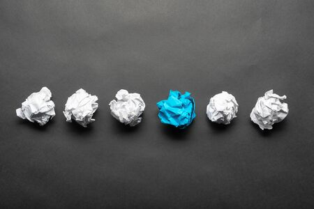 Crumpled blue paper ball among white balls on black background. Extraordinary solution of problem. Think outside the box. Business motivation with copy space. Unique idea among failing ideas metaphor Stock fotó