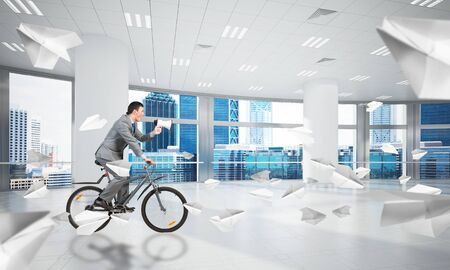 Man in business suit riding bicycle at conference hall with flying paper planes. Businessman with megaphone on bike at office . Business presentation and announcement. Cyclist speaking in loudspeaker