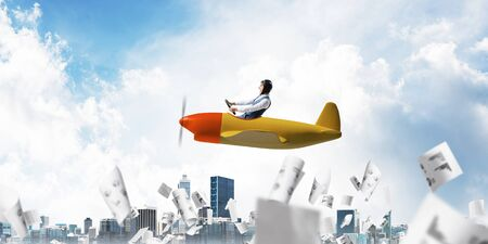 Business accounting and statistics concept with funny pilot. Aviator driving propeller plane above falling paper sheets with infographics. Young man flying in small airplane above paperwork. Stok Fotoğraf