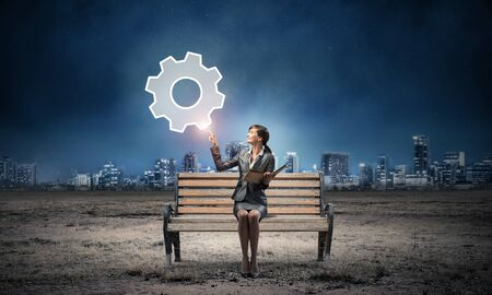 Young woman holding open book on wooden bench outdoor. Beautiful girl finger pointing at gearwheel symbol in night sky. Modern cityscape panorama at night. Engineering and development concept