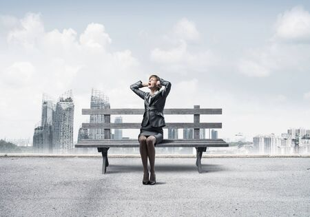 Stressful woman sitting on wooden bench. Emotional screaming girl keeps hands on head. Businesswoman in despair on background modern cityline panorama with cloudy sky. Woman call for help. Stock Photo