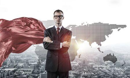 Joven empresario seguro vistiendo capa roja contra el fondo de la ciudad moderna
