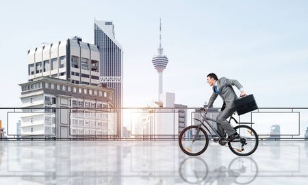 Man wearing business suit riding bicycle on penthouse balcony. Young cyclist with suitcase on background of business district. Terrace with modern downtown view. Time management and business activity Reklamní fotografie