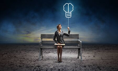Young woman with open book on wooden bench outdoor. Business education and idea generation. Girl holding at light bulb illuminated symbol in night sky. Beautiful skyscape with deep blue night sky Imagens