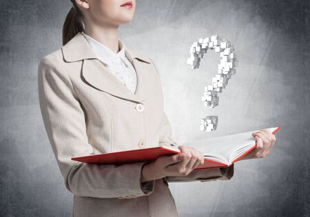 Attractive woman holding open notebook with question mark. Business consultation and legal assistance. Elegant young woman in white business suit with open book in hands on background of grey wall. Stock fotó