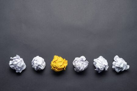 Crumpled yellow paper ball among white balls on black background. Extraordinary solution of problem. Business motivation with copy space. Unique and different experience. Idea generation