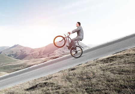 Businessman riding downhill by bike. Nature landscape with copy space. Man in business suit riding bicycle on mountain road. Cyclist popped wheelie on background of blue sky. Healthy lifestyle