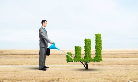 Businessman watering green plant in shape of financial graph at field. Business analytics and statistics. Friendly ecosystem for business and investment. Business growth and development. Stok Fotoğraf