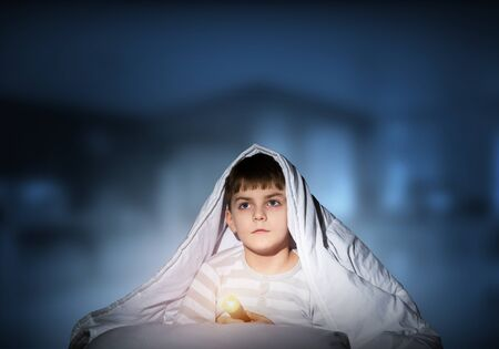 Serious child with flashlight hiding under blanket. Attentive kid lying in his bed at home. Fear to sleep in darkness at night. Portrait of little boy in pajamas on deep blue blurred background.