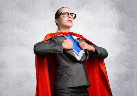 Señora de negocios joven atractiva en capa de héroe rojo sobre fondo de pared gris. Retrato de super heroína de mujer de negocios. Desarrollo profesional y liderazgo. Súper mujer segura de sí misma lista para nuevos desafíos. Foto de archivo