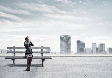Young woman sitting on wooden bench outdoors. Girl in business suit keeps hands on face for surprise. Hide from problems. Help and successful solutions. Modern cityline panorama with cloudy sky.