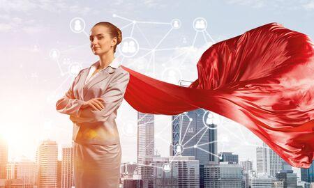 Junge selbstbewusste Geschäftsfrau mit rotem Umhang vor modernem Stadthintergrund