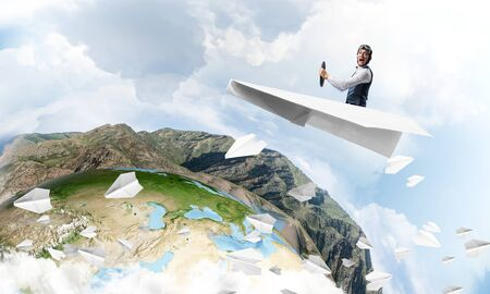 Pilot in leather helmet and goggles driving paper plane on background of blue cloudy sky. Traveling around the world. Funny man flying in small paper airplane. Earth horizon with high mountain range