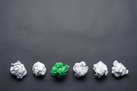 Crumpled green paper ball among white balls on black background. Extraordinary solution of problem. Think outside the box. Business motivation with copy space. Unique idea among failing ideas metaphor