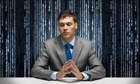Young serious man folded hands and sitting at desk. Portrait of businessman wears business suit and tie on binary matrix code background. Modern digital technologies and big data flow.