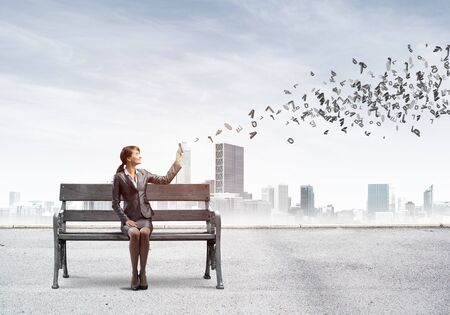 Young woman with smartphone sending text message. Girl sitting on wooden bench on background modern city panorama. Various letters flying out from mobile phone. Mobile marketing and communication Stock Photo