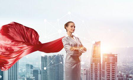 Jeune femme d'affaires confiant portant une cape rouge sur fond de ville moderne Banque d'images