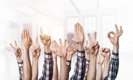 Fila de manos de hombre mostrando varios gestos. Ok, señalar con el dedo, victoria, dedos abiertos, puño cerrado y signos de pulgar hacia arriba. Manos humanas gesticulando sobre fondo claro borroso. Muchos brazos alzados juntos. Foto de archivo