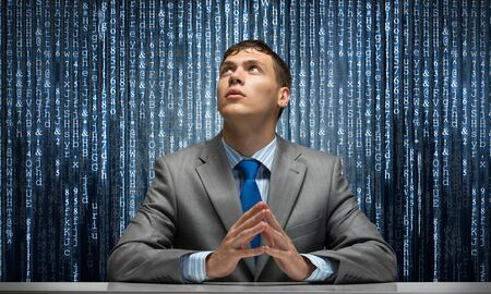 Man with folded hands looking upward. Young businessman sitting at desk. Programmer wears business suit and tie on background cyberspace with digital falling lines. Future innovation technology