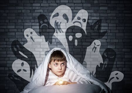 Frightened child with flashlight hiding under blanket. Halloween scary ghostly monsters on wall. Scared kid in pajamas lying in his bed at home. Fear of the dark. Little boy can not sleep at night. Reklamní fotografie - 126857766