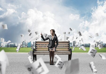 Business woman taking selfie photo or chatting with smartphone. Attractive girl using mobile phone on wooden bench. Mobile marketing and communication. Cityline panorama with falling paper documents