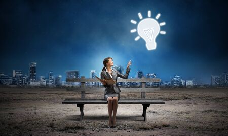 Young woman holding open book on wooden bench outdoor. Beautiful girl finger pointing at light bulb symbol in night sky. Modern cityscape panorama at night. Business education and idea generation