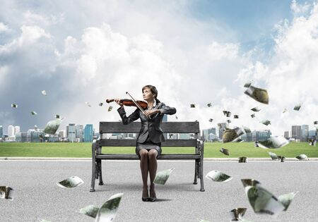 Young woman with violin sitting on wooden bench. Attractive businesslady playing violin. Modern cityline panorama with falling money banknotes. Musician practicing and performing outdoors.