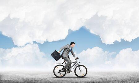 Mann mit Business-Anzug Fahrrad fahren im Freien. Radfahrer mit Koffer auf dem Hintergrund des blauen Himmels. Zeitmanagement und Geschäftstätigkeit. Geschäftsmann, der zur Arbeit eilt. Geschäftswettbewerb und Karriere