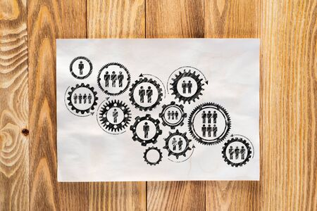 Corporate social responsibility concept with group of rotating gears and cogs. Human resources cooperation sketch on wooden surface. Workplace with sheet of paper lying on wooden desk.