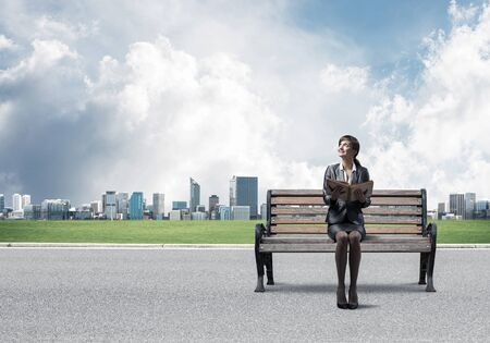 Young woman holding open book and sitting on wooden bench outdoors. Beautiful girl in business suit looking up on background modern cityline panorama in sunny day. Business education and growth.