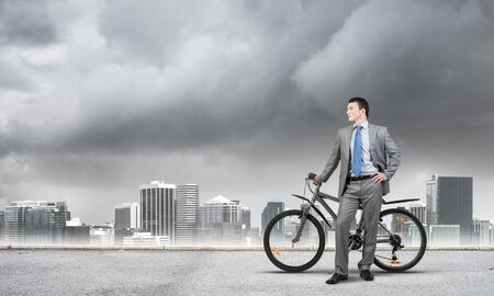 Young man wearing business suit and tie standing on asphalt road with bike. Businessman with bicycle on background of storm sky above megalopolis. Male cyclist holding bicycle, having break in riding.