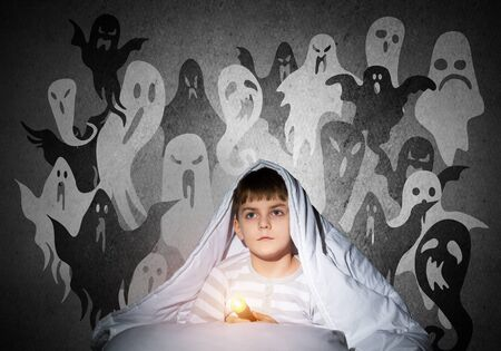 Little child with flashlight hiding under blanket. Halloween scary ghostly monsters on wall. Adorable kid lying in bed at home. Young boy can not sleep at night. Portrait of cute boy in pajamas.