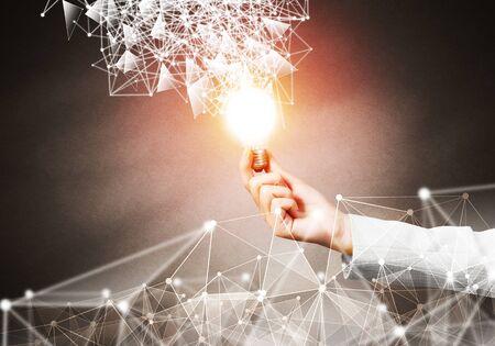 Mano de mujer sosteniendo bombilla incandescente y estructura de red abstracta sobre fondo de pared oscura. Investigación científica y solución innovadora. Concepto de comunicación de internet y tecnología de nube global