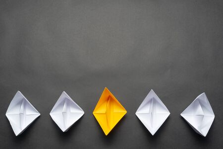 Row of paper ships on black background. Business concept of creative innovation and leadership. Flat lay yellow origami boat in group of white boats. Social marketing layout with copy space.