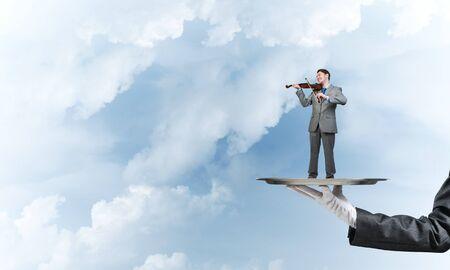 Mano de camarero que presenta en bandeja hombre tocando el violín
