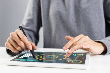 Woman using tablet computer for financial data analysis. Close-up of female hand holding pen and touching screen of tablet device. Online stock trading application. Mobile smart device in business