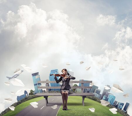Young woman with violin sitting on wooden bench. Attractive businesslady playing violin. City panorama with round horizon of world and flying paper planes. Musician practicing and performing outdoors.