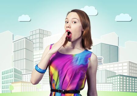 Surprised young female model with red hair. Shocked european woman hiding open mouth behind hand and feeling amazed. Elegant flirty lady in colorful dress and bracelets on background cartoon cityscape Imagens