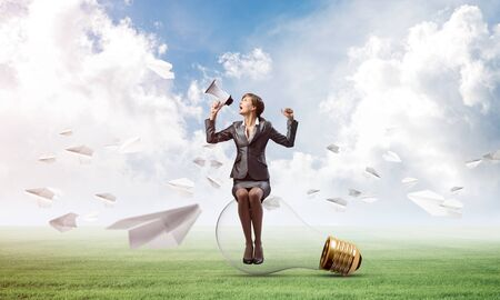 Young woman with megaphone sitting on lightbulb. Female speaker advertising new service or product on green meadow with flying paper planes. Businesslady shouting in loudspeaker. Business announcement Stock Photo